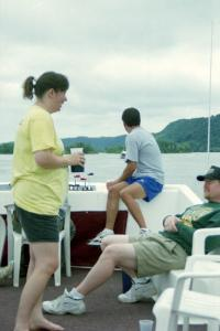 Shelly Hanson and Kurt Ristow converse while Eric Thompson looks out over the Mississippi River