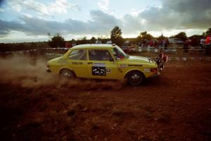 The Tom Bier / Ole Holter SAAB 99 through the spectator corner at sundown.