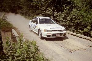 Greg Healey / John MacLeod Subaru Impreza at speed over a bridge on SS5, Magalloway North.