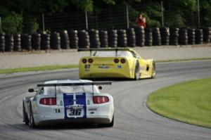 Cliff Ebben's Ford Mustang chases Doug Peterson's Chevy Corvette through the carousel