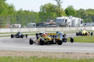 Formula cars stream through the carousel on the pace lap.