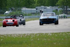 Brian Kennedy's Ford Mustang Boss 302 passes Tom Daly's and Phil Schaefer's Austin-Healey Sprites