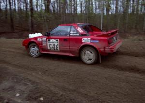 Steve Irwin	/ Phil Schmidt power out of a 90-left on SS2 in their Toyota MR2.