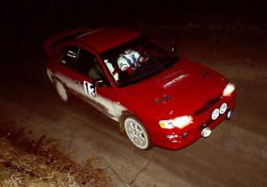 Piotr Wiktorczyk / Ray Summers at speed at night in their Subaru Impreza.