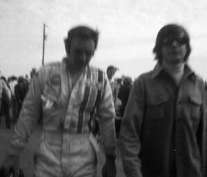 Peter Revson walks back to the pits after retiring.