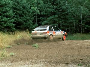 Jeff Zwart / Cal Coatsworth in their Mazda 323GTX hit the gas at the exit of a hairpin.