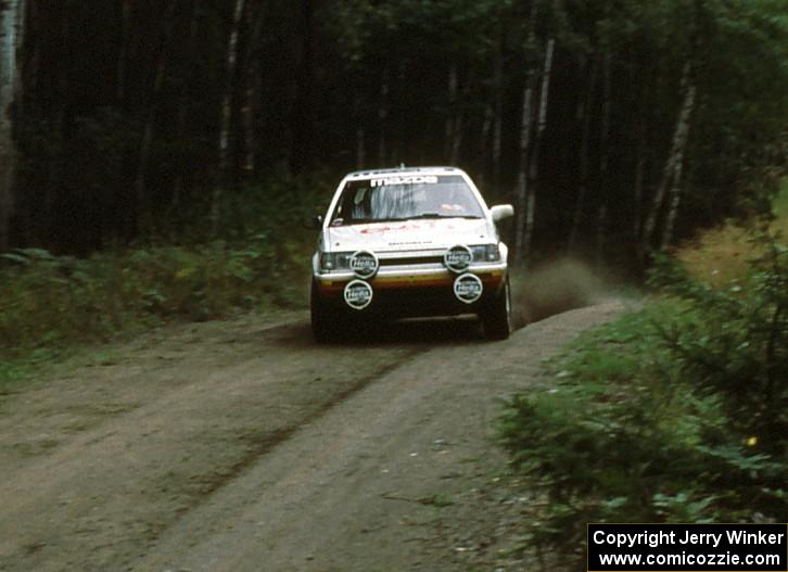 Rod Millen / Tony Sircombe fly over a crest in preparation for an upcoming 90 right in their Mazda 323GTX.