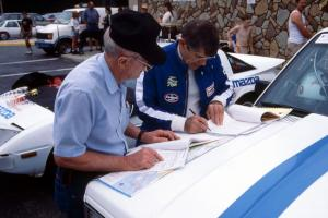 Ken Stewart goes over notes with a crew member(?) on the hood of the Chevy S-10 he and Doc Shrader shared.