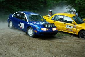 Ryan Johnson / Matt Himes Saturn SL2 passes the stuck Erik Payeur / Adam Payeur Mitsubishi Galant on SS1. Both later DNF'ed.